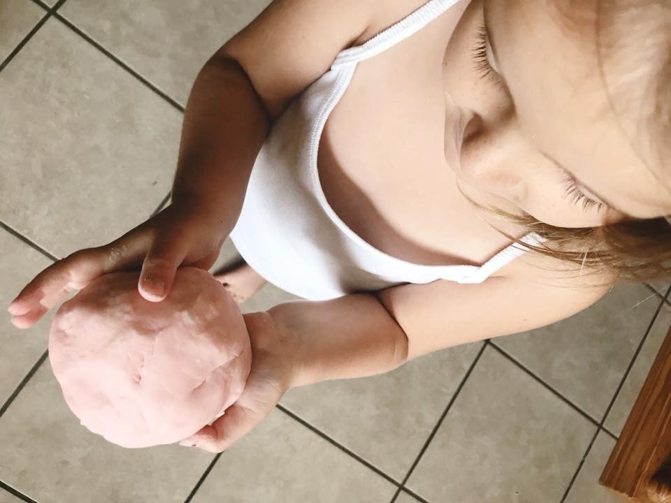 girl holding homemade playdough