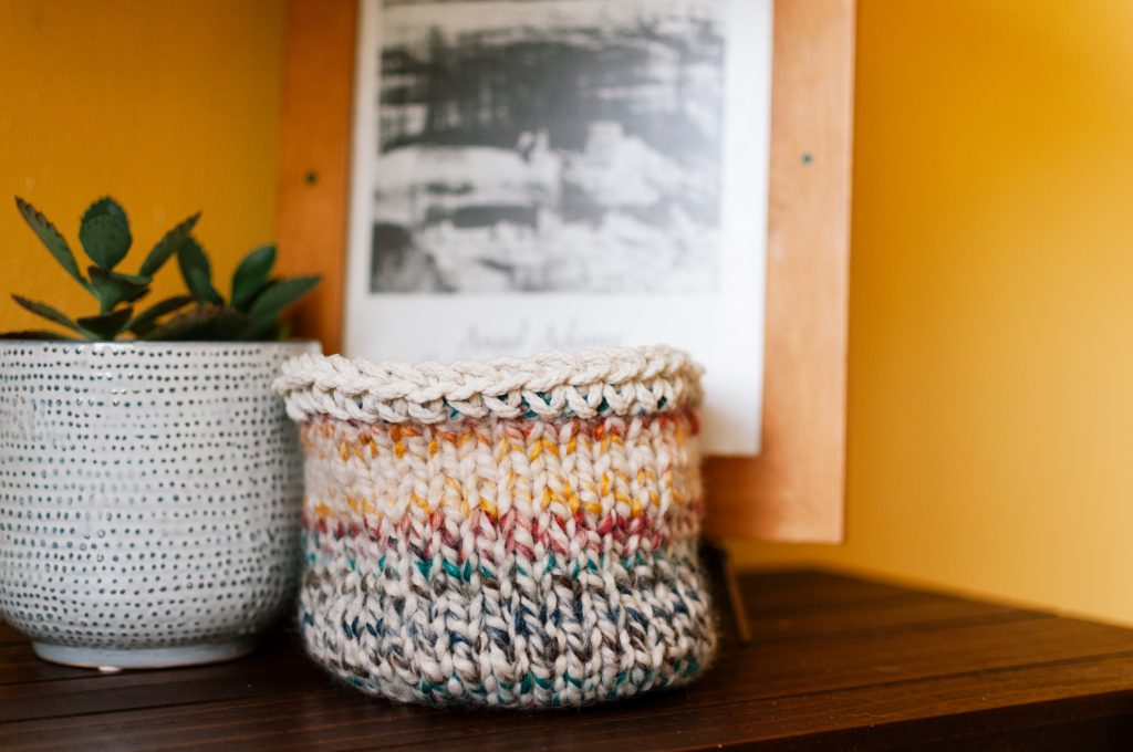 knit basket on a shelf with a plant