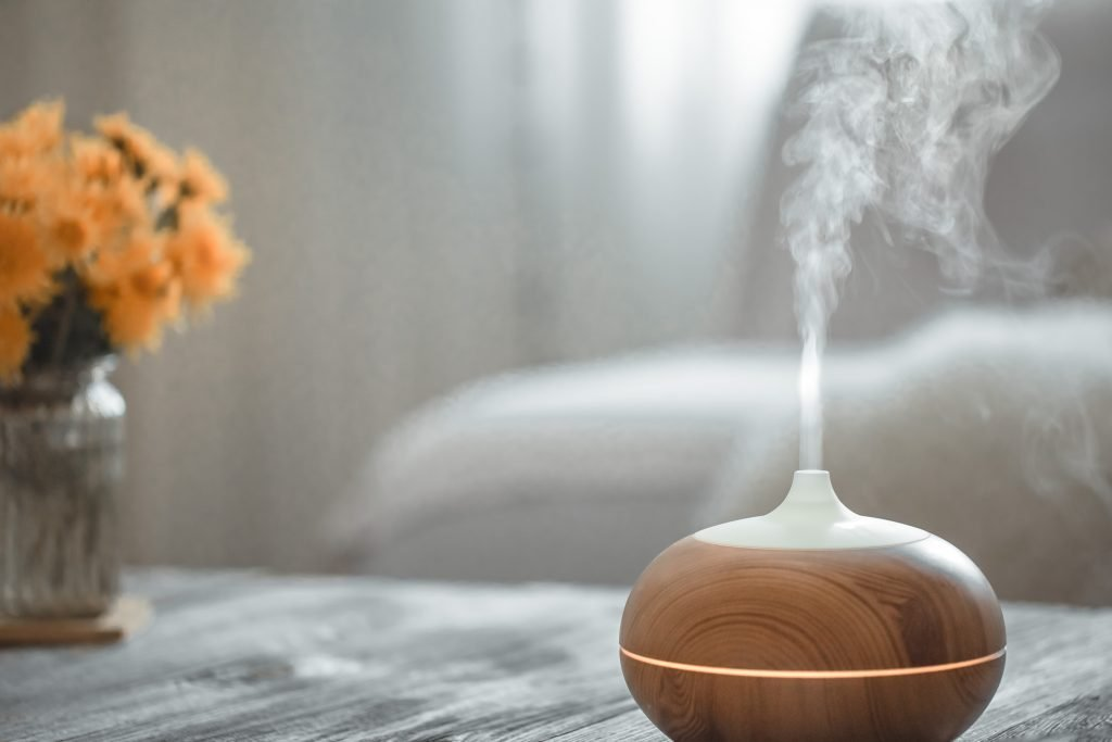 essential oil diffuser on coffee table with vase of yellow flowers