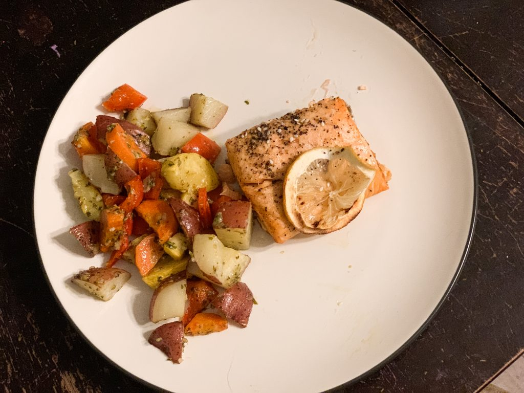 plate with roasted vegetables with pesto and salmon